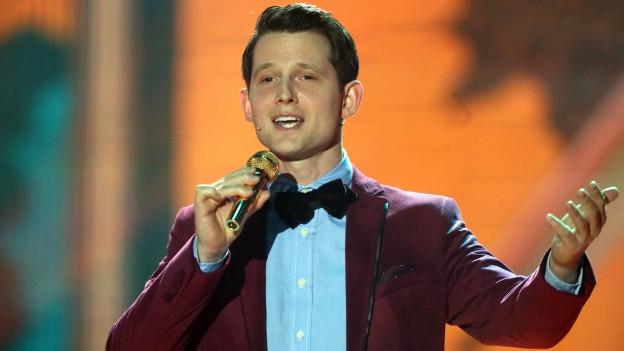 Junger Mann in rotem Sacko und Fliege spricht in ein goldenes Mikrofon
