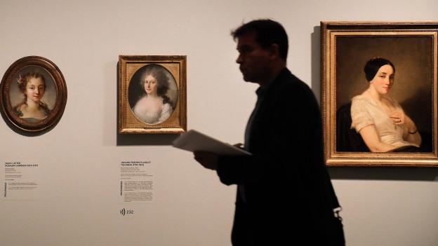 Drei Gemälde von Frauenportraits in einem Museum, davor im Schatten geht ein Mann