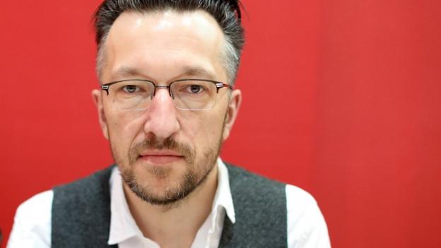 Ein Mann mit Brille vor rotem Hintergrund.