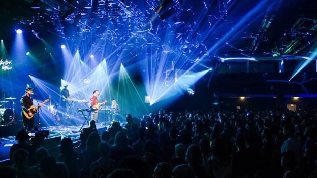 Eine Band performt live vor einer Menschenmenge
