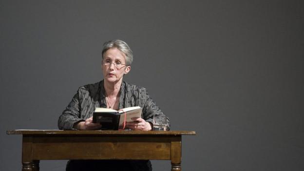 Die Autorin sitzt an einem Holztisch und liest aus ihrem Buch