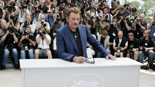 Hunderte Kameras richten sich auf den Rücken eines Mannes, der an einem Tisch sitzt und in die Kamera schaut