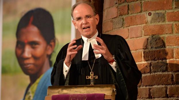 Ein Pfarrer predigt, im Hintergrund das Bild einer südasiatischen Frau