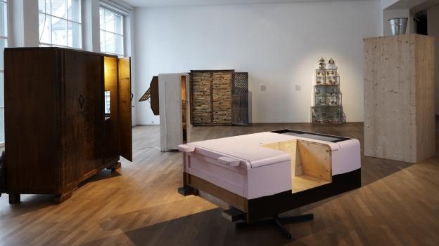 In einem Ausstellungsraum stehen mehrere Schränke mit unterschiedlichen Funktionen
