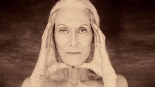 Eine alte Frau schaut mit durchdringendem Blick in die Kamera, mit den Händen rahmt sie ihr Gesicht