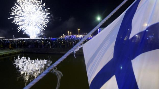 Die finnische Flagge vor einem Feuerwerk