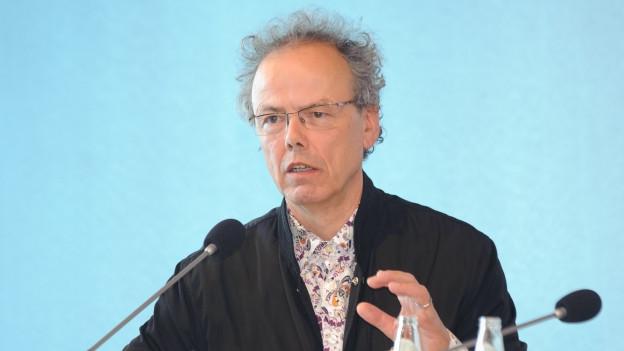 Ein Mann mit grauen Locken sitzt an einem Konferenztisch und spricht in ein Mikrofon