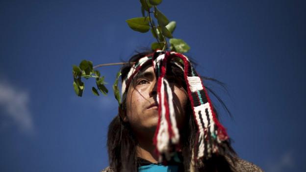 Ein Mapuche mit gewebten Bändern und Ästen als Kopfschmuck