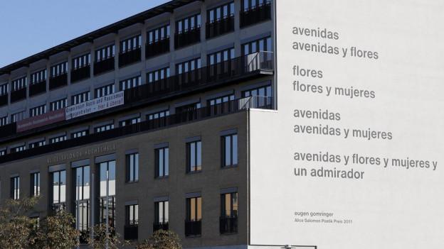 An einer weissen Hausfassade prangt das Gedicht in grossen schwarzen Lettern