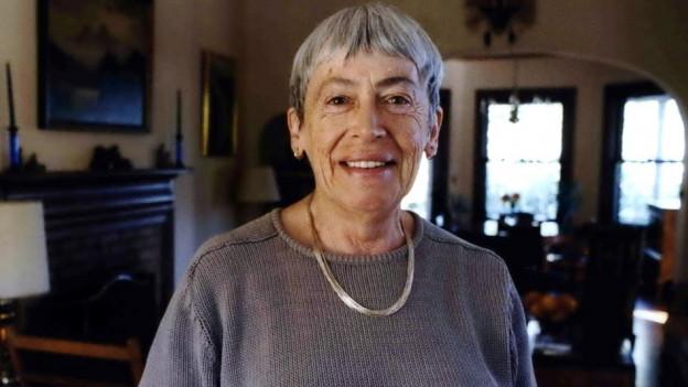 Eine Dame mit kurzen grauen Haaren und fliederfarbenem Pullover steht in einer Wohnstube