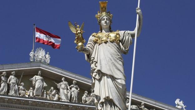 Heroische Frauenstatue mit Flagge von Österreich im Hintergrund