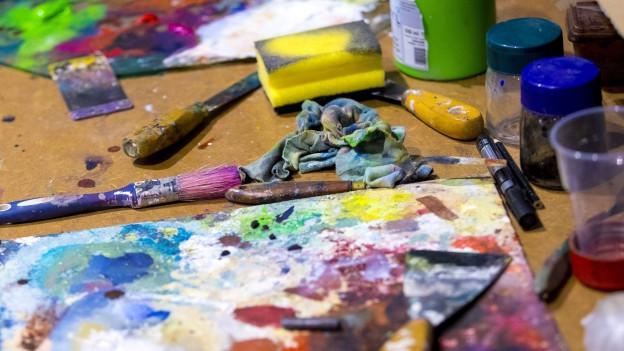 Arbeitsfläche mit Pinsel und Farben.