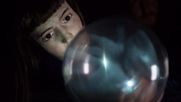 Eine Puppe blickt in eine Glaskugel.