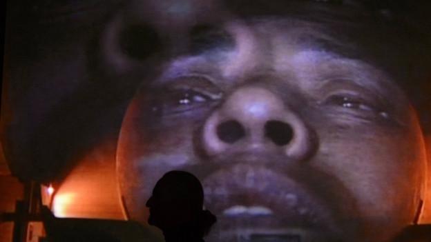 Gesicht eines Mannes an eine Hausfassade projiziert