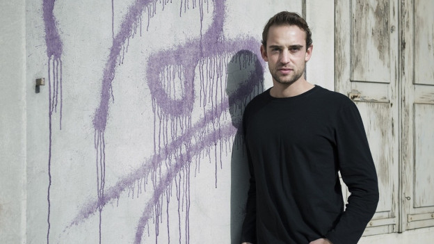 Junger Mann steht vor einer weissen, mit Grafitti bemalten Wand und schaut in die Kamera