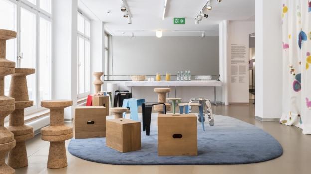 Ein Lichtdurchfluteter Raum mit grossem Teppich unf verschiedenen ausgefallenen Sitzgelegenheiten