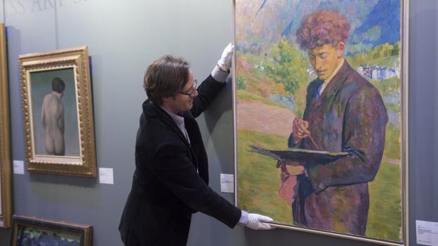 Museumsmitarbeiter hält Gemälde eines jungen Mannes