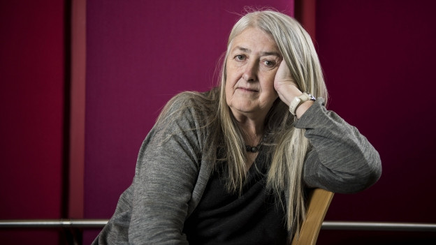 Dame mit langen, weissblonden Haaren sitzt nachdenklich auf einem Stuhl