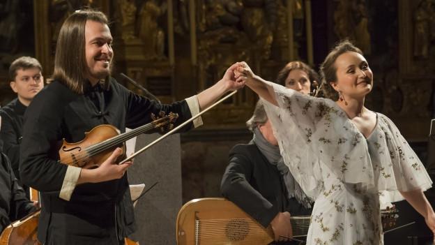 Ein Mann mit Violine in der Hand und eine Frau in weissem Kleid verbeugen sich vor Publikum