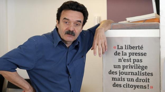 Mann mit schwarzen Haaren und Schnautz lehnt an einem Poster mit der Aufschrift «La liberté de la presse n'est pas un privilège des journalistes mais un droit des citoyens!»