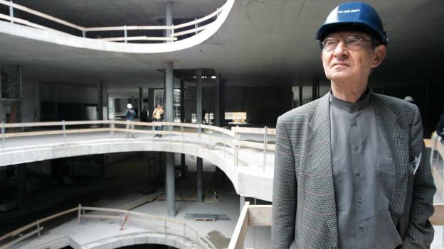 In grau geleideter Herr mit Bauhelm in einem mehrstöckigem Gebäude