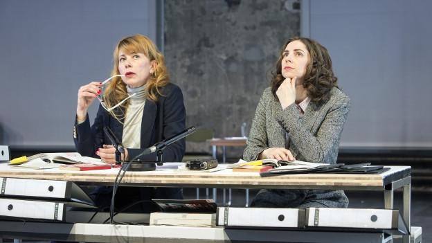 Zwei Frauen sitzten an einem Schreibtisch, vor ihnen Notitzhefte, Aktenordner, Aufnahmegeräte