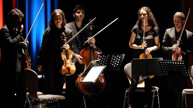 Ein Streicherquintett, in der MItte ein junger Mann mit Cello