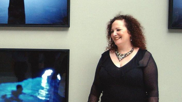 Frau mit langen, dunkelroten, lockigen Haaren und schwerer Kette