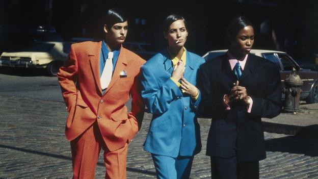 Drei Personen in bunten Anzügen