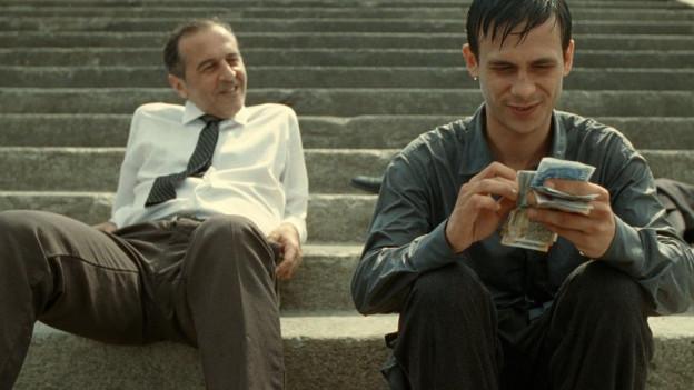 Ein Mann hält ein Bündel Geldnoten in den Händen