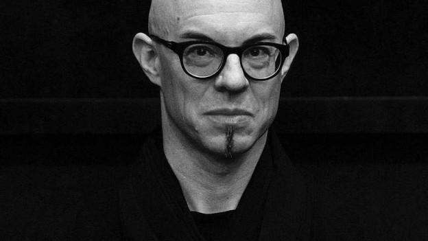 Ein Schwarz-Weiss-Foto eines Mannes mit Glatze