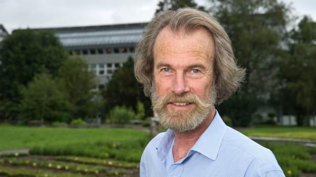 Ein Mann um die 50 mit halblangen Haaren und Vollbart trägt ein Hemd und steht in einem Garten.