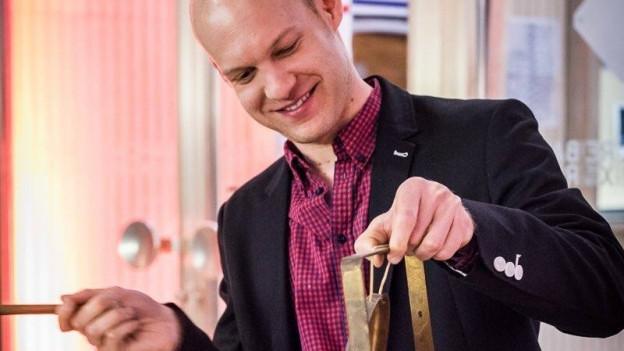 Ein junger Mann schlägt lächelnd auf einen kleinen Gong.