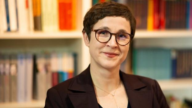 Eine Frau mit kurzen Haaren und Brille steht vor einem Bücherregal.