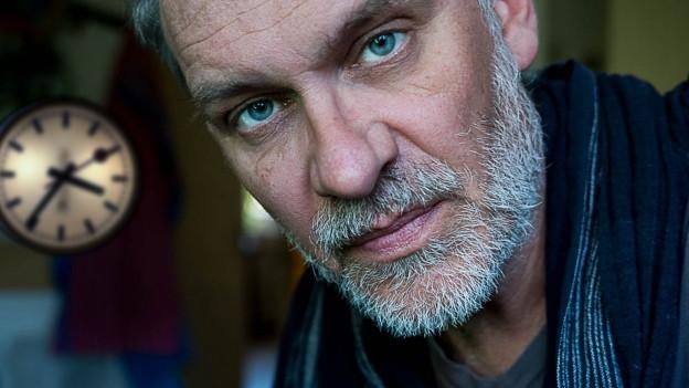 Ein Mann um die 50 mit kurzem weissem Bart und blauen AUgen schaut ernst in die Kamera.