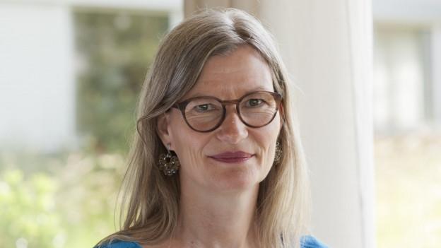 Frau mit langen grauen Haaren und Brille lächelt in die Kamera