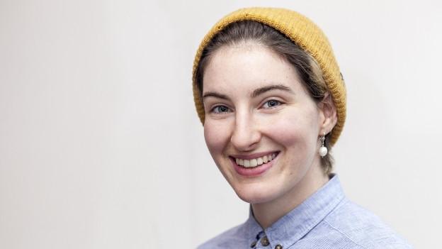 Frau mit gelbr Mütze, blauem Hemd lächelt in die Kamera