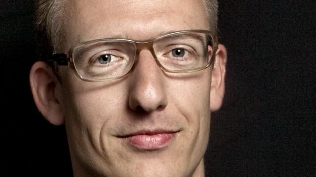 Mann mit Brille vor schwarzem Hintergrund