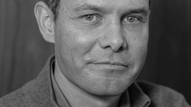 Mann mit Brille schaut in die Kamera, Nahaufnahme Portrait, schwarzweiss