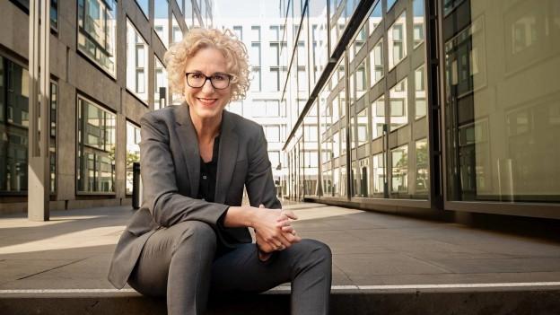 Frau mit blonden Haaren und grauem Anzug sitzt auf einer Treppe zwischen mehreren Hochhäusern.