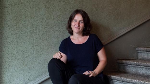 Eine Frau blickt - auf einer Treppe sitzend - in die Kamera