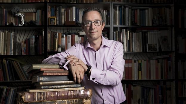 Ein Mann blickt in die Kamera und stützt sich auf Büchern ab