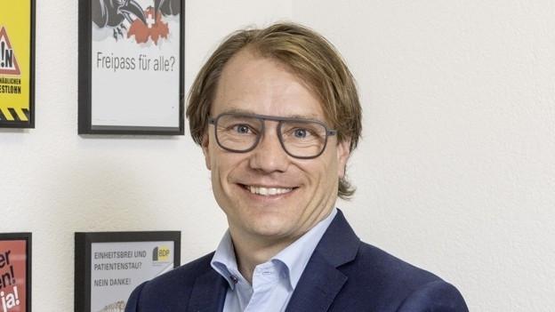 Ein Mann mit Brille blickt in die Kamera