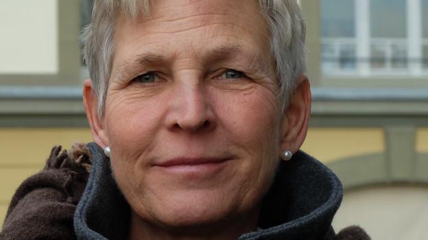 Eine Frau mit kurzen, grauen Haaren blickt in die Kamera