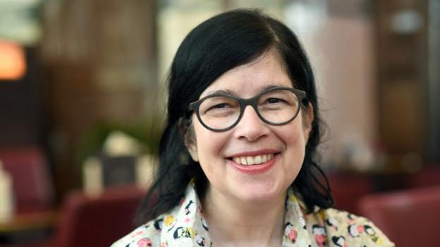 Frau mit schwarzen Haaren und runder Hornbrille lächelt in die Kamera
