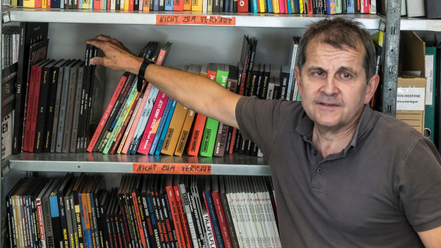 Mann Mitte Vierzig steht vor Regal mit vielen verschiedenen, farbigen Heftern