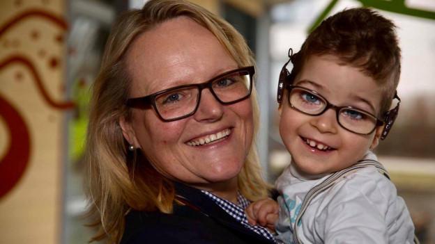Frau mittleren Alters mit blonden Haaren und dunkler Brille mit jungem Kind in den Armen