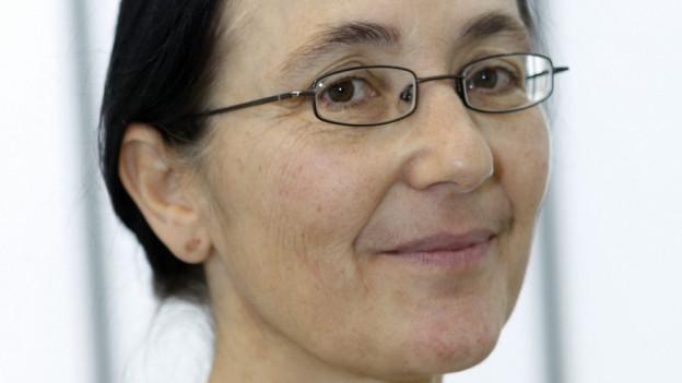 Frau mit dunklen, streng nach hinten gebundenen Haaren und Brille