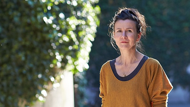 Frau in orangem Pullover draussen vor Grünem Hintergrund.