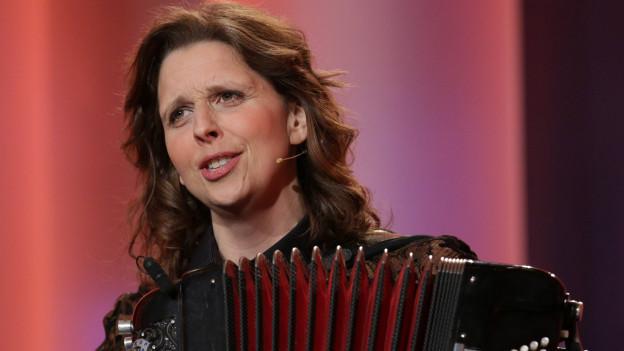 Frau mit längeren, braunen Haaren und Handorgel in der Hand auf der Bühne
